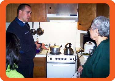firefighter teaching an elderly woman about fire safety in her kitchen