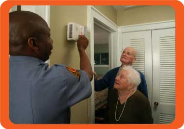 fire service member helps seniors with fire prevention